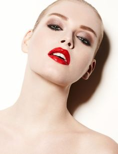 High-gloss red lips, with slicked back blonde hair, luminescent skin and lined eyes, with shimmery brown eyeshadow
