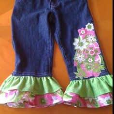 Embellished jeans. Some sewing required. Take apart inside seam on legs. Choose your material for the flowers then iron onto wonder under. Cut out design then iron into place. Then sew around the edges of the flowers. Sew on ruffles then sew seam back together.
