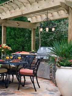 This fabulous outdoor space includes a cooking station with grill, refrigerator and smoker, which is set in stacked stone beside a large dining table. A chandelier hangs from the pergola, a great asset for dining at dusk.