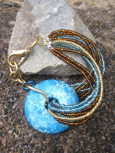 Beaded Jewelry. Now this is what I call a statement bracelet! A bright turquoise gemstone with turquoise, gold, and brown seed beads! Great with Jeans and a Tee! Check out the link for more color options and matching necklaces! Winter colors now on sale! 50% off the regular price of $29!