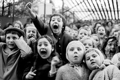 """Children watch the story of """"Saint George and the Dragon"""" at an outdoor puppet theater in Paris, 1963."""