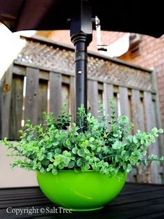 Create a planter that fits on your patio table pole using dollar store materials.