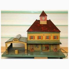 Bing, circa 1926-29. Lithographed sheet metal railway station with candle lighting, clock towers, and flag (not in the picture); open passage hall with central lock and chains , 4 double opening doors. Marked: Int Reg Trademark BW Made in Germany.