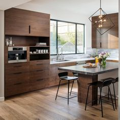 Designed for maximum durability, this modern kitchen by Kristianne Watts includes rich walnut cabinets, Silstone countertops and sleek, stainless appliances. A small island and rustic dining table ensure plenty of spaces to eat and entertain. Source by Small Modern Kitchens, Modern Farmhouse Kitchens, Farmhouse Style Kitchen, Modern Kitchen Design, Rustic Kitchen, Interior Design Kitchen, Kitchen Ideas, Kitchen Decor, Kitchen Inspiration
