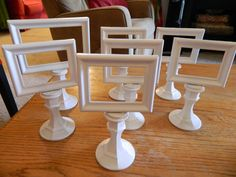 DIY Table Signs. Small frames mounted on short candlesticks, all painted white.