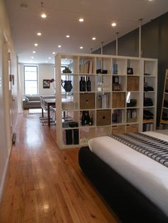 """Large bookshelf is both functional and serves as a dividing point between the """"bedroom"""" and """"living room"""" spaces in this studio"""