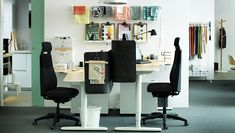Dos mesas BEKANT con divisores en gris oscuro en el centro de una oficina blanca con unas telas en la pared.