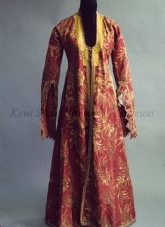 L. 19C - E 20C Turkish Yelek, woman's open coat (robe) of dark red silk embroidered overall with couched gold thread in leaf and floral pattern, scoop neck with buttons at bust, trimmed with gold braid, as are pocket slits, long sleeves open and zig-zag to elbow, trimmed with gold braid. Lined with pink cotton with red and green leaf pattern in stripes. Kent State University Museum