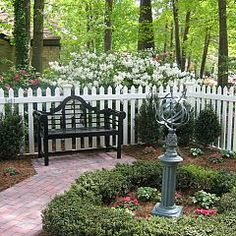 Lutyens bench, white picket fence, brick pavers, boxwood