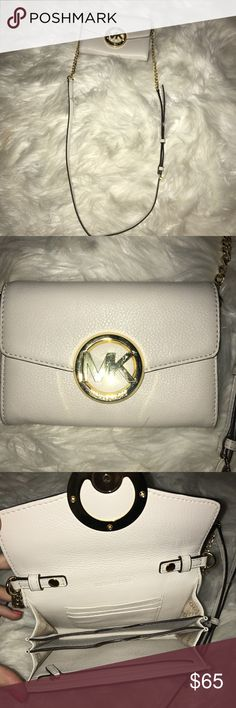 Micheal Kors cross body clutch This lightly used Micheal Kors cross body clutch is a super cute accessory that matches any outfit! An easy access clutch fits all your needs when you're out and about! The white leather with gold designs adds to any outfit! Michael Kors Bags Crossbody Bags