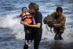 A volunteer holds a Syrian child after arriving with a group of migrants on a dinghy from the Turkish coast to the northeastern Greek island of Lesbos, on Wednesday, Sept. 30, 2015. The International Organization for Migration says a record number of people have crossed the Mediterranean into Europe this year, now topping a half a million, with some 388,000 entering via Greece. (AP Photo/Santi Palacios)