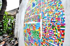 Abstract collage of Beijing neighborhoods creates a colorful stencil on dilapidated courtyard wall
