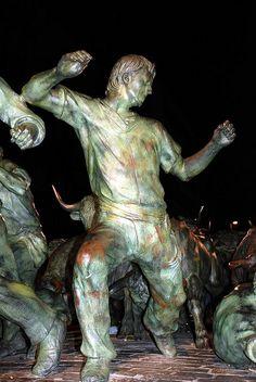 Pamplona - Monumento al Encierro    Monumento al Encierro en la Avenida de Roncesvalles.    Obra hecha en bronce que mide 11 metros de largo por 4 de ancho- Fue diseñada por el artista Rafael Huerta, y mira directamente a la Plaza de Toros de Pamplona.    Se pueden ver 6 toros, 3 cabestros y 11 mozos corrriendo delante.    Más sobre Pamplona en http://www.callesdepamplona.es