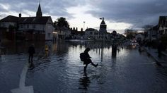Flooded homes along the River Thames are being evacuated and thousands more are at risk, as a political row over the crisis deepens.