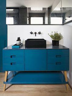 Také v koupelně je dřevěný lakovaný nábytek v petrolejové barvě.