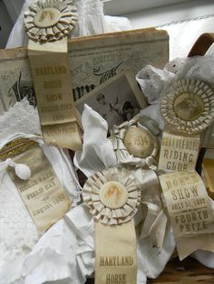 Antique creamy horse ribbons displayed on an old literary newspaper with frothy white linens!