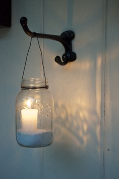 Mason jar votive candle holders at night - could attach this to anything, i.e. beam, pillar, fence, etc...