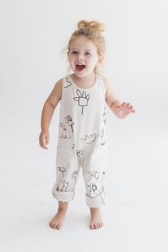 Quirky wildflower print on white jersey overalls. Snaps at shoulder and two big pockets. See also Hatched Jumpsuit. Materials: 100% cotton jersey - Designer: Jacqueline Sage - Care: Machine wash cold,