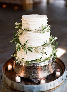 Three tier textured wedding cake wrapped with olive branches: http://www.stylemepretty.com/virginia-weddings/madison-virginia/2016/09/09/indoor-charlottesville-farm-style-wedding/ Photography: Ashley Cox - http://ashleypcox.com/