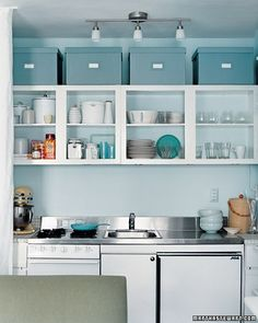 How to decorate above cabinets - The boxes colored to blend in with the wall sort of fill in that space without creating a heavy, contrasting, eye-catching visual. Simply brilliant.