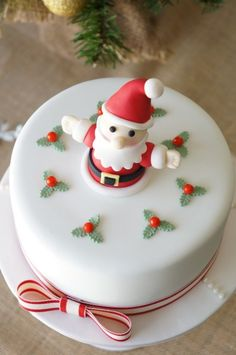 Santa cake Created by twolittlefigs cakes.Noel christmas cake. Fondant cake, white and red.Fondant christmas decorations, fondant santa , wreaths and edible red cacous. chocolate mud cake.