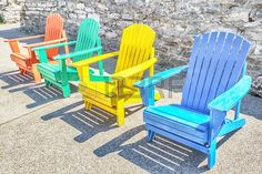 Brightly colored adirondack chairs arranged in a row Bright sun lights them  Stock Photo