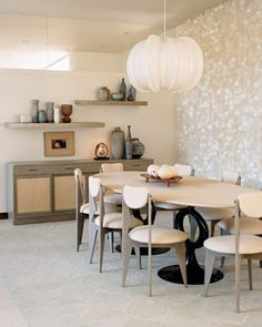A capiz-shell curtain creates a shimmering backdrop in the dining area, which is mostly soft whites and cool grays, including custom-made chairs by Minassian, a circa-1950 cabinet by Edward Wormley, ceramics by local potters from the '50s, and a rice-paper light fixture by artist Stephen White.