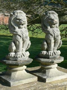 """A pair of part-weathered, composition-stone lions, sitting upright and on octagonal plinths. Condition note: one lion has on old repair through the middle of its body. modern 14"""" x 14"""" x 35"""" high overall £240 for the pair"""