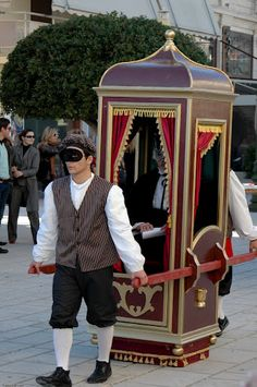 Arrival of an honored guest, Venetian style. One person carriage carried by masked servants.