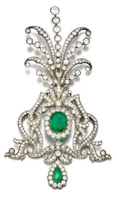EMERALD AND DIAMOND AIGRETTE, 1900S. Of open work scroll design set with circular-cut diamonds, centring on an oval-shaped emerald, suspending a pear-shaped emerald drop, fittings deficient.
