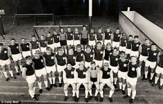 The 1964 squad, including Geoff Hurst, Harry Redknapp and Bobby Moore, pose on the Upton Park terraces