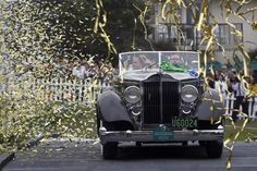 Confetti streams down as Joseph Cassini and his daughter Caroline Cassini drive on stage to receive the Best of Show award for their 1934 Packard 1108 Twelve Dietrich Convertible Victoria at the Concours d'Elegance on the 18th fairway of the Pebble Beach Golf Links in Pebble Beach, California, August 18, 2013. Cassini's wife Margie sits in the back seat. The Concours tops a week-long celebration of automobiles and car culture on the Monterey Peninsula. REUTERS-Michael Fiala