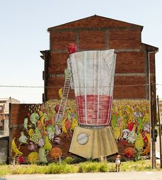 """Street artist Blu recently painted this mural of anthropomorphic fruits & veggies cheerfully jumping into a juicer of doom for the DesordesCreativas festival in Ordes, Spain. According to the festival's site, this piece is a """"declaration of intent and a plea to vegetarianism"""". You may remember we have posted several of Blu's murals in the past, including Spaghetti Brain Eating Man, Infinite Pickpocket, Big Bang Big Boom, and more."""