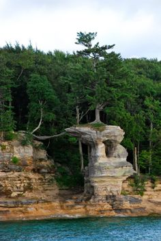 Chapel Rock is a sandstone structure located on the shores of Lake Michigan, in the Pictured Rocks National Park (USA). A large pine inexplicably grows on top of this rock with little or no feeding ground for rooting. Lago Michigan, Michigan Usa, Munising Michigan, Beautiful World, Beautiful Places, Foto Nature, Picture Rocks, Unique Trees, National Parks Usa