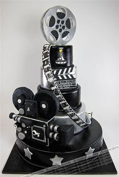 Movie Theme Cake - movie projector, reels, film strips, multi tier cake in black and silver, topped with a movie reel.  Who would even want to cut it?