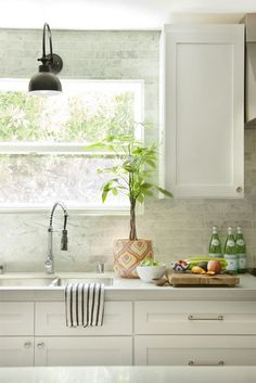 This is such a beautiful kitchen - I love the white and soft grey - so restful!  Amber Lewis DIYed this sconce from a HomeGoods lamp she found on clearance. It looks so chic!  Very clean but cosy looking