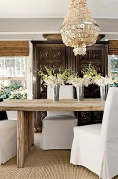 Love the texture - rug , shades rustic table, shell chandelier