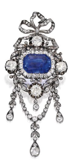 *GOLD, SILVER, SAPPHIRE AND DIAMOND BROOCH Centering a buff-top emerald-cut sapphire weighing 16.96 carats, within a bow motif frame set with numerous old mine and single-cut diamonds weighing approximately 6.85 carats; circa 1890; together with an 18 karat white gold rope chain for wear as a pendant. #SapphirePendant