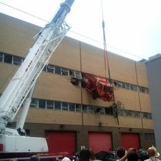 A New York Department of Sanitation salt-spreading truck that crashed through a wall on the second floor of  a repair shop in the Queens borough of New York is supported by a crane. Firefighters used a cherry-picker to rescue the driver.