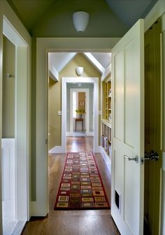 The well-worn wood floors here connect to the walls with very simple flat-stock baseboard trim. In fact, the whole home style here reflects a transitional mentality by surrounding the traditional four-panel doors with flat stock trim that dies smoothly into the baseboard — with no traditional plinth-block at the bottom.