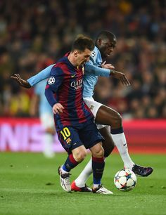Lionel Messi of Barcelona is challenged by Yaya Toure of Manchester City during the UEFA Champions League Round of 16 second leg match between Barcelona and Manchester City at Camp Nou on March 18, 2015 in Barcelona, Catalonia.