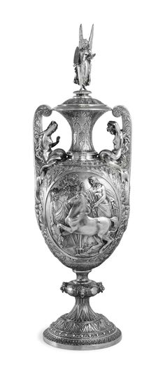A MONUMENTAL EDWARD VII SILVER VASE MARK OF HANCOCKS & CO., LONDON, 1909. Vase-shaped on a circular foot, the stem with knop applied with lion masks, the body chased with acanthus, with two mythological scenes, the first depicting the Contest of Athena and Poseidon, the second depicting Hercules rescuing the princess Hesione, the handles formed as a pair of nereids.