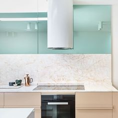 Mirrored surfaces and shining marble bounce light around this luxe-looking Melbourne  kitchen, created by designer Fiona Lynch (fionalynch.com.au). By adding shades of green and warm putty tones  she has brought an individual flair to what was a simple, white, contemporary space
