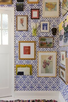 Royal blue and white graphic wallpaper + chunky white molding + gallery of frames and art