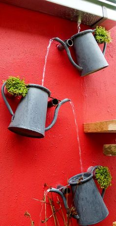 Fantastic cascading watering can feature. Great way to create a decorative drainage system from the gutter.