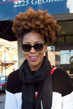 Ebony girl has a fun natural hairstyle and wears a black and white pullover