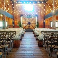 The ceremony set up was spectacular. Vintage nail kegs filled with baby's breath lined the aisle. The wooden chairs added so much character! Styled, set up, floral and rentals by On The Side Events & Service.