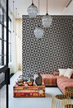 hanging pendant lanterns + eclectic fabrics juxtaposed with a wall of black + white tiling - a true eye for style.