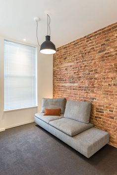 The micro flat features a single exposed brick wall in the living area