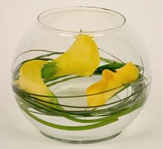White callas with lily grass spiraled in a bubble bowl half way filled with water.    I'm thinking about something like this with blue flowers and a candle in the middle.